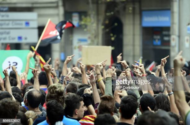 Demonstrators gesture as they protest called by CNT union in front of the Catalan Popular Party headquarters during a general strike in Catalonia...