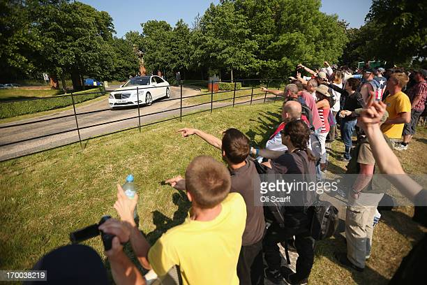 Demonstrators gesture from the protester encampment as vehicles arrive at The Grove hotel which is hosting the annual Bilderberg conference on June 6...