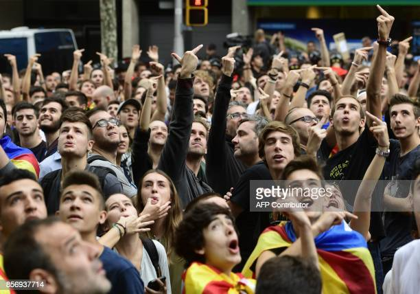 Demonstrators gesture to a helicopter overflying a protest called by CNT union in front of the Catalan Popular Party headquarters during a general...