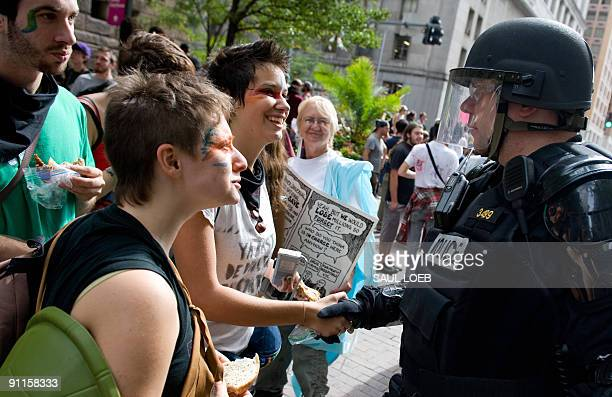 Demonstrators greet a police officer dressed in riot gear prior to joining thousands of marchers through downtown Pittsburgh Pennsylvania September...