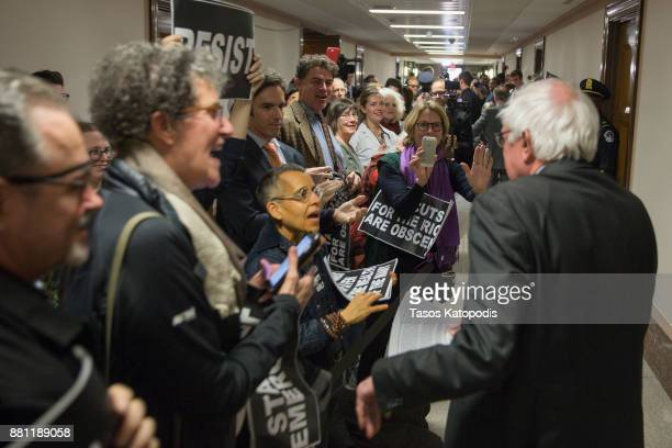 Demonstrators greet Sen Bernie Sanders on his way to the full committee markup of the FY2018 Reconciliation Legislation on November 28 2017 in...