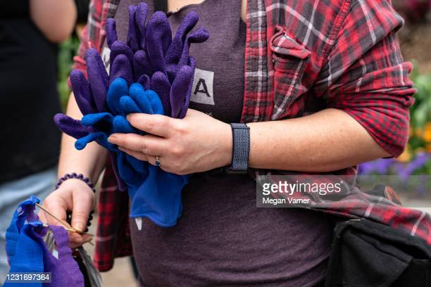 Demonstrators hand out gloves and streamers before marching through downtown in honor of Breonna Taylor on March 13, 2021 in Atlanta, Georgia. Today...