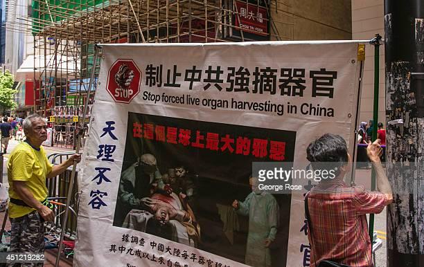 Demonstrators hang a billboard protesting illegal organ transplants in the Times Square neighborhood on May 25 in Hong Kong China Hong Kong with a...