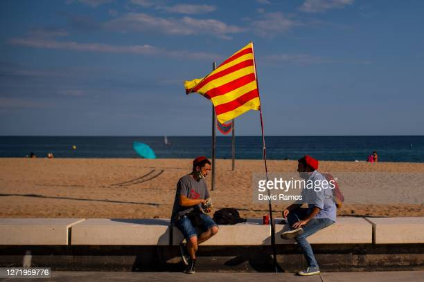 Demonstrators have a drink next to a Catalan flag at the corniche during a Catalan Pro-Independence demonstration on September 11, 2020 in Badalona...