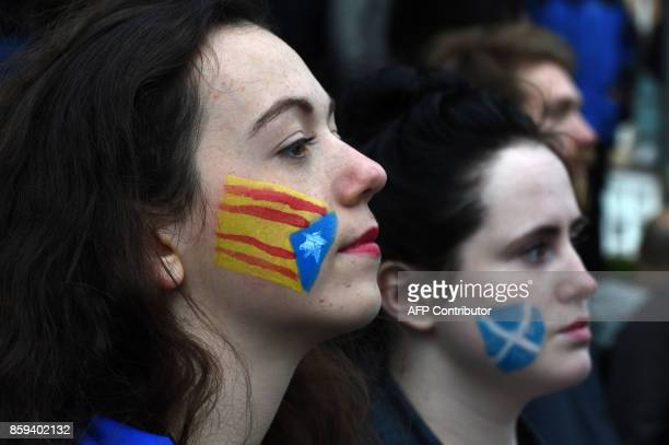 Demonstrators have the Catalan proindependence 'Estelada' flag and the Flag of Scotland the Saltire painted on their faces during a protest to show...