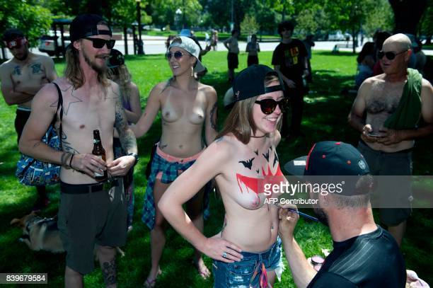 Demonstrators have their breasts and chests painted prior to the start of the 2017 GoTopless Day Parade on August 26 2017 in Denver Colorado Founded...