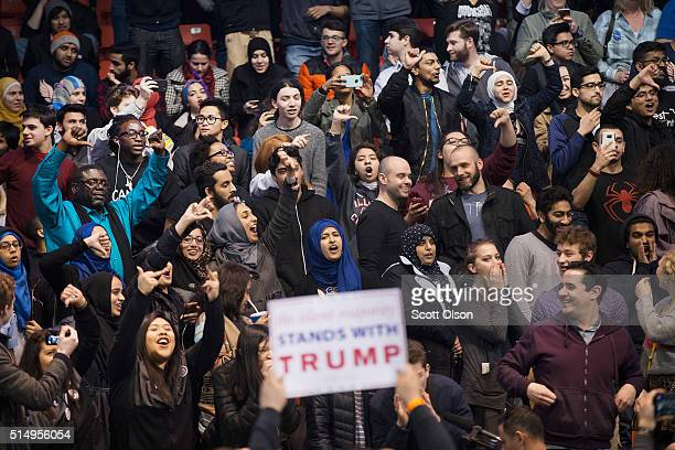 Demonstrators heckle a supporter of Republican presidential candidate Donald Trump before the start of a rally at the University of Illinois at...