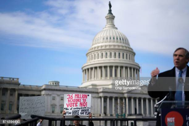 Demonstrators hoist signs as Sen Jeff Merkley addresses a rally against the proposed Republican tax reform legislation on the east side of the US...