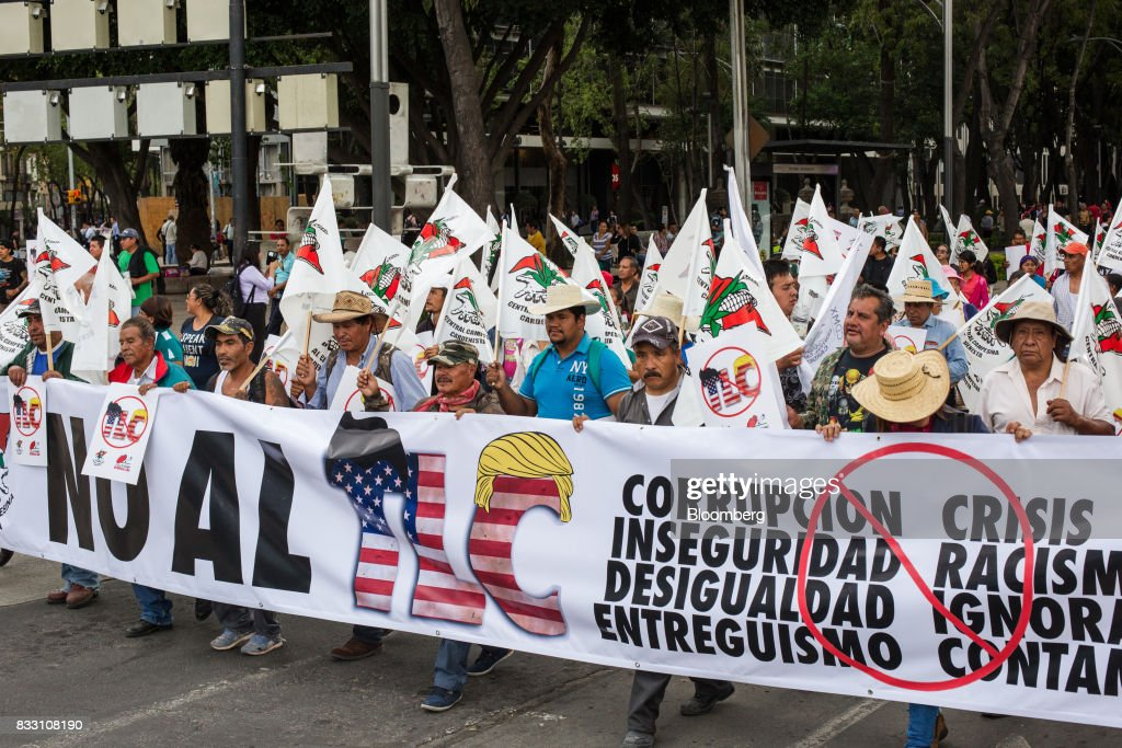 Demonstrators hold a banner and flags during a protest against the North American Free Trade Agreement (NAFTA) in Mexico City, Mexico, on Wednesday, Aug. 16, 2017. U.S. Trade Representative Robert Lighthizer made clear Wednesday, on the first day of Nafta renegotiation talks with Mexico and Canada, that the administration will push to win back the jobs and manufacturing capacity the U.S. lost under Nafta. Photographer: Brett Gundlock/ Bloomberg