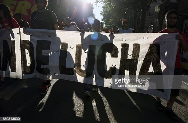 Demonstrators hold a banner as they march for the 15th anniversary of former President Fernando de la Rua ousting in Buenos Aires on December 20,...