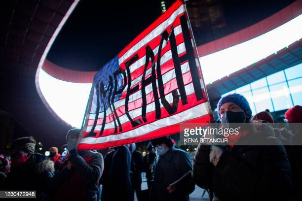 Demonstrators hold a banner calling for impeachment of US President Donald Trump during a protest outside the Barclays Center in Brooklyn, New York...