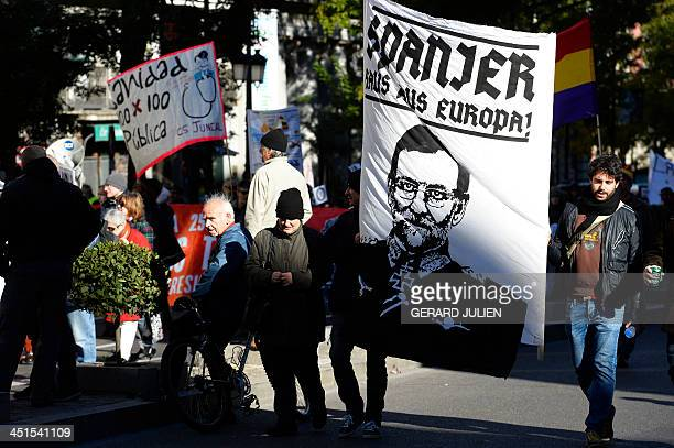 Demonstrators hold a banner depicting Spanish Prime Minister Mariano Rajoy and reading in German 'Spaniard leave Europe' during a protest against the...