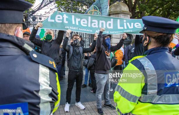 Demonstrators hold a banner during a protest against the Irish government imposed restrictions put in place to help stem the rise in the number of...