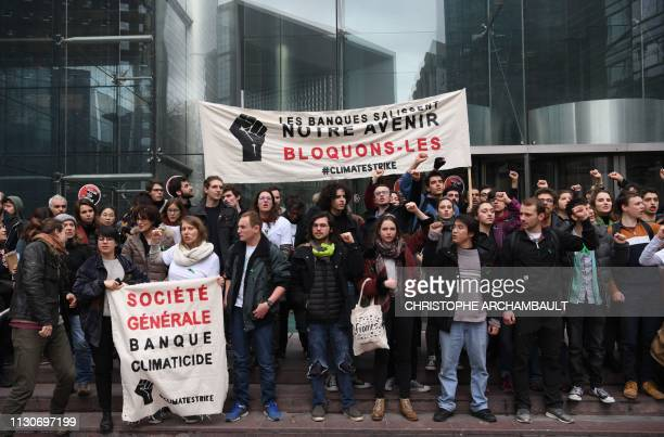 "Demonstrators hold a banner reading ""Banks dirty our future. Let's block them"" outside the building of the Societe Generale bank headquarters in La..."
