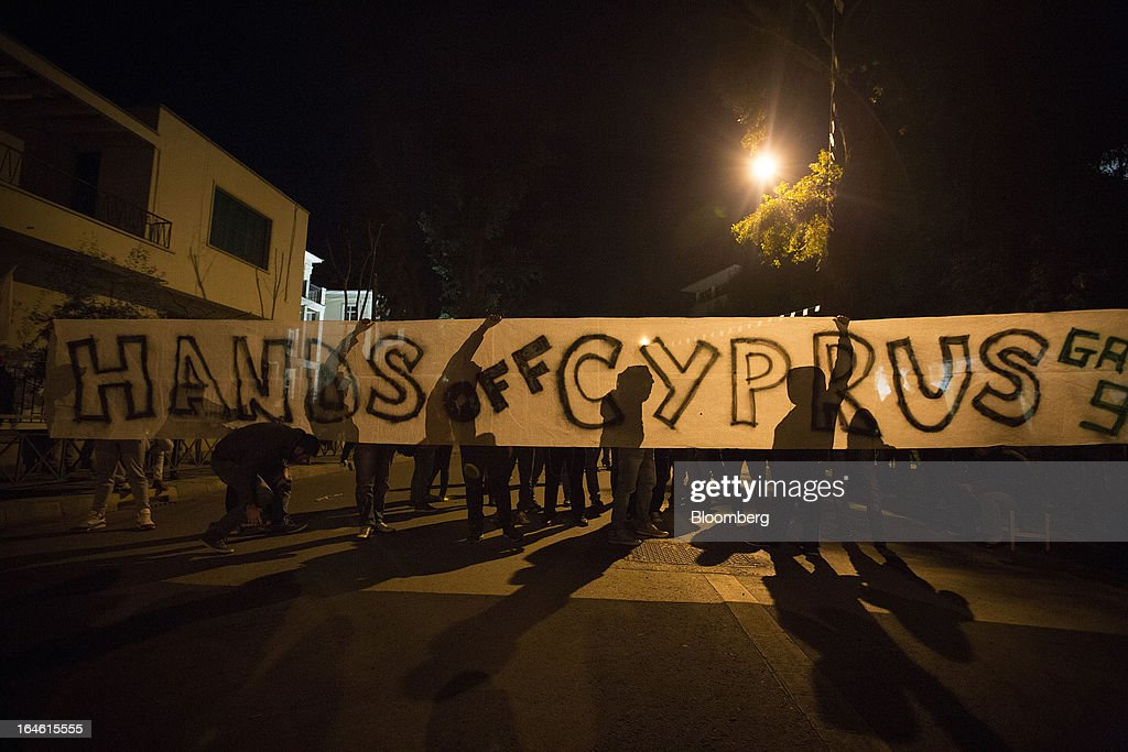 Demonstrators hold a banner reading 'Hands off Cyprus' during a protest outside the European Union House in Nicosia, Cyprus, on Sunday, March 24, 2013. Cyprus's fate hangs in the balance as euro-area finance ministers meet today to decide whether the tiny Mediterranean island has done enough for a bailout that will avert its financial collapse. Photographer: Simon Dawson/Bloomberg via Getty Images