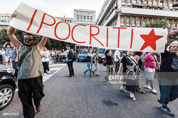 Demonstrators hold a banner reading 'hypocrites' as they take part in an antimafia rally to protest against the ostentatious funeral of the purported...