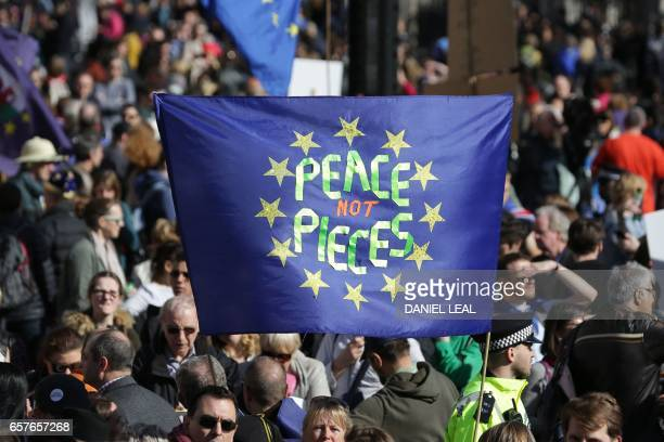 Demonstrators hold a banner with 'Peace not pieces' written on an EU flag in Parliament Square during an antiBrexit proEuropean Union march in...