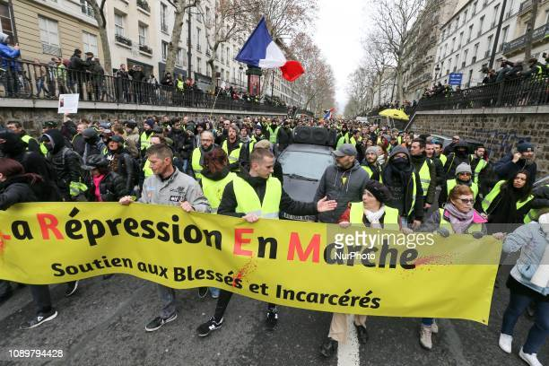 Demonstrators hold a bannerd reading quotThe repression en marchequot during an antigovernment demonstration in Paris on January 26 2019 called by...