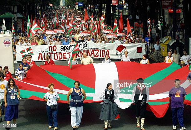 Demonstrators hold a big 'Ikurrina' Basque flag and a banner reading 'No Apartheid Autodetermination' during a march organized by the banned Basque...