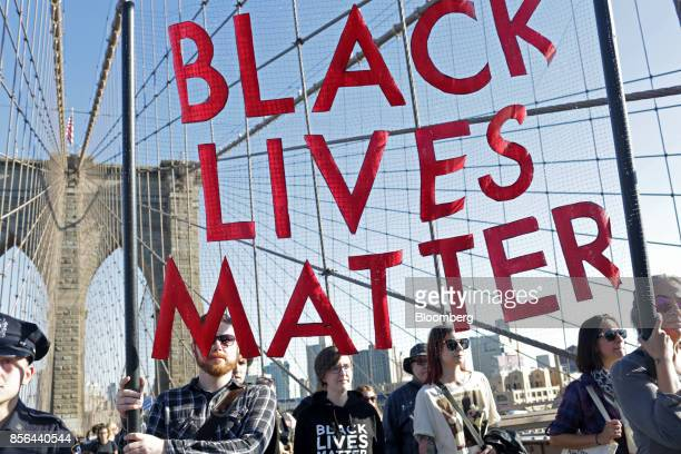 Demonstrators hold a Black Lives Matter banner while participating during the March for Racial Justice on the Brooklyn Bridge in the Brooklyn borough...