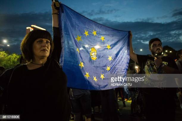 Demonstrators hold a European flag during a gathering in front of the Romanian Prime Minister's office building on June 21 2018 in Bucharest Romania...