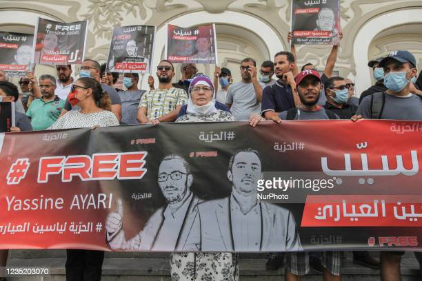 Demonstrators hold a giant banner that reads free Yassine Ayari, and placards that read in Arabic release Yassine Ayari, during a demonstration held...