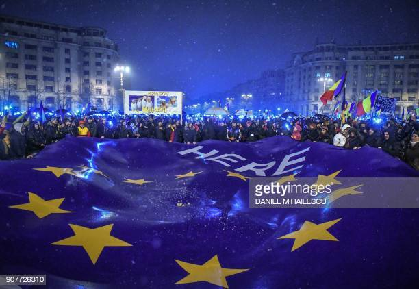 Demonstrators hold a giant flag of the European Union as they stage an anti-government and anti-corruption protest in front of the Romanian...