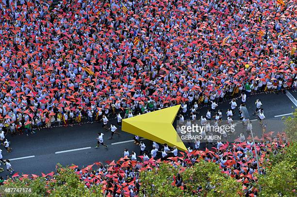 Demonstrators hold a giant yellow cursor on Meridiana street as others wave 'Esteladas' flags during celebrations of Catalonia's National Day which...