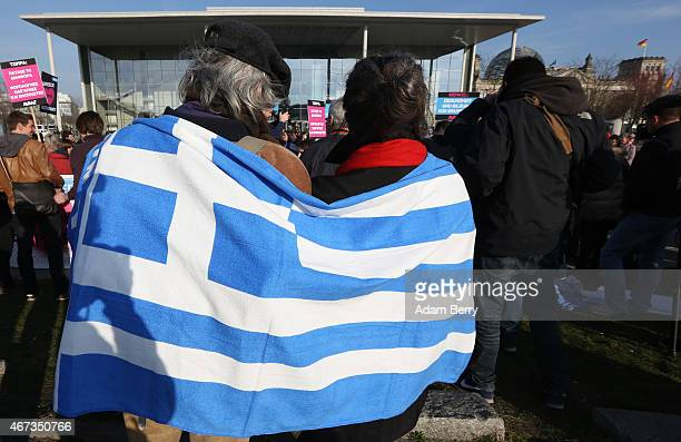 Demonstrators hold a Greek flag as they take part in a protest between the German federal Chancellery and the Bundestag prior to a meeting between...