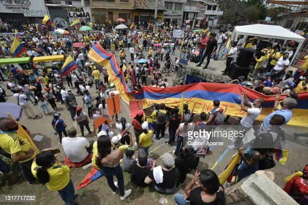 Demonstrators hold a large Colombian flag at Loma de la Cruz as they march through Cruz de la Loma towards Universidad del Valle of the march at La...