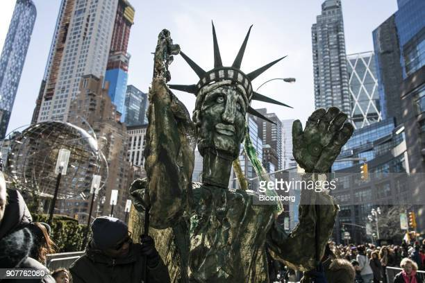 Demonstrators hold a large hand made figure in the likeness of the Statue of Liberty at Columbus Circle during the Women's March on New York City in...
