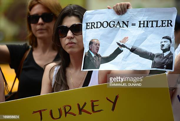 Demonstrators hold a photo of Turkish Prime Minister Recep Tayyip Erdogan comparing him to Adolf Hitler as part of a protest in solidarity of...