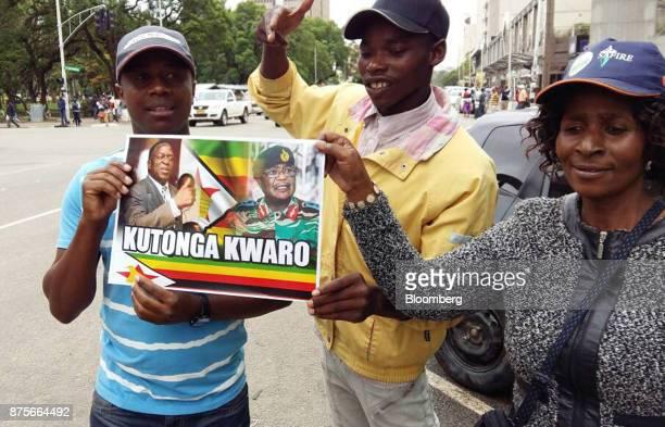 Demonstrators hold a placard depicting Emmerson Mnangagwa Zimbabwes former vicepresident left and ConstantineChiwenga commander of the Zimbabwe...