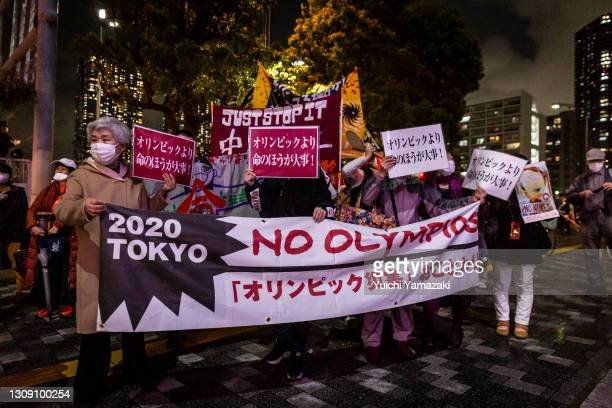 Demonstrators hold a placard during a protest against the Tokyo Olympics on March 25, 2021 in Tokyo, Japan. Japan's nation-wide torch relay for the...