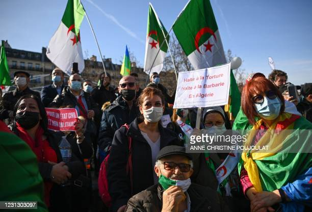 Demonstrators hold a placard reading 'Halt torture, halt barbarism in Algeria' and wave Algerian national flags during a rally in Paris on February...