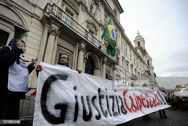 """Demonstrators hold a placard reading """"Justice trampled"""" in front of Brazil's embassy to protest Brazilian President Lula's refusal to extradite..."""