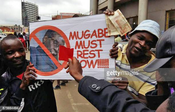 Demonstrators hold a placard reading 'Mugabe Must Rest Now' as they call for the resignation of president Robert Mugabe in Harare Zimbabwe on...