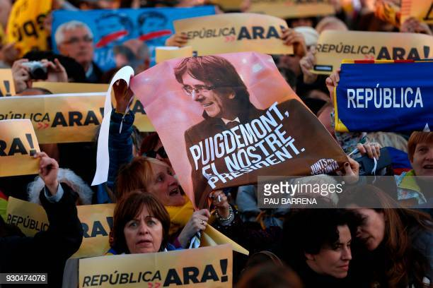 Demonstrators hold a poster of Catalonia's deposed leader Carles Puigdemont along with signs reading 'A republic now' during a protest called by the...