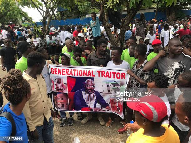Demonstrators hold a poster portraying Liberian President George Weah as they gather outside the Liberian Mansion in Monrovia on June 7, 2019 during...