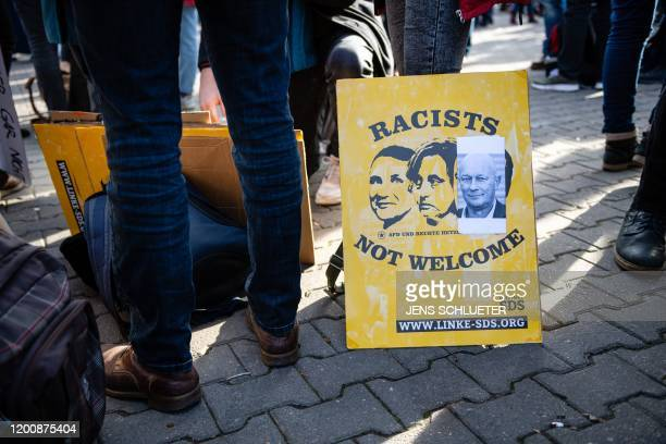 Demonstrators hold a poster showing Afd politicians Bjoern Hoecke and Beatrix von Storch and FDP politician Thomas Kemmerich that reads Racists not...