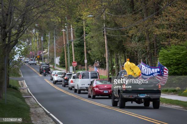 Demonstrators hold a Rolling Car Rally in front of Democratic Governor Ned Lamont's residence while protesting the state's stayathome order to combat...