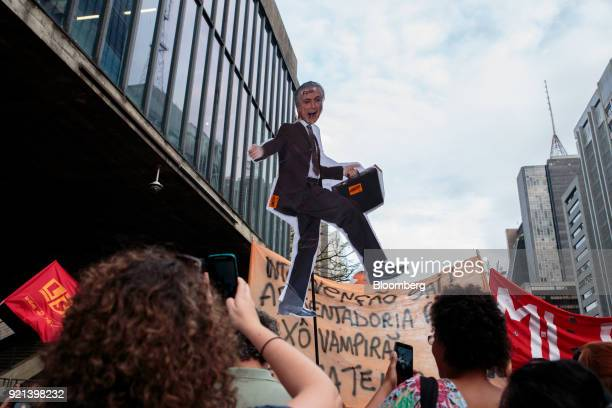 Demonstrators hold a sign displaying the image of President Michel Temer with the word 'Out' written on it during a protest against pension reform in...