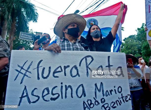 Demonstrators hold a sign reading Assassin rat out during a protest against corruption and lacks in the health system, demanding the resignation of...