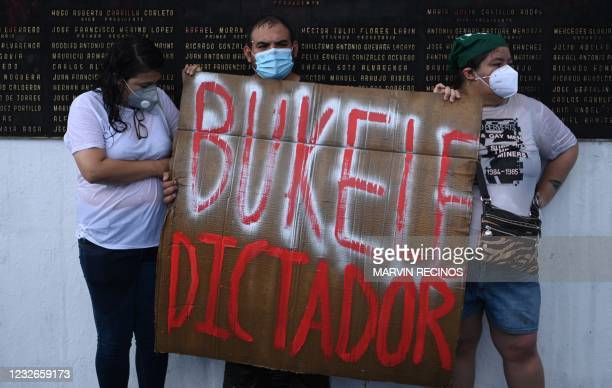 Demonstrators hold a sign reading Bukele Dictator, referring to Salvadoran Prsident Nayib Bukele, during a protest against the latest measures taken...