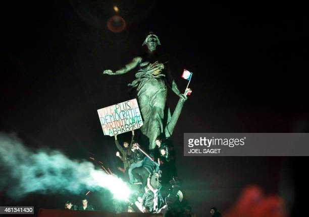 Demonstrators hold a sign reading 'Hurry more democracy everywhere against barbarism' as they gather at Place de la Nation during the unity rally...