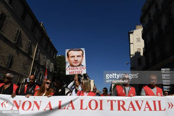 TOPSHOT Demonstrators hold a sign reading 'No to labour law' ''dog of employers union ' and bearing a picture of French President Emmanuel Macron...