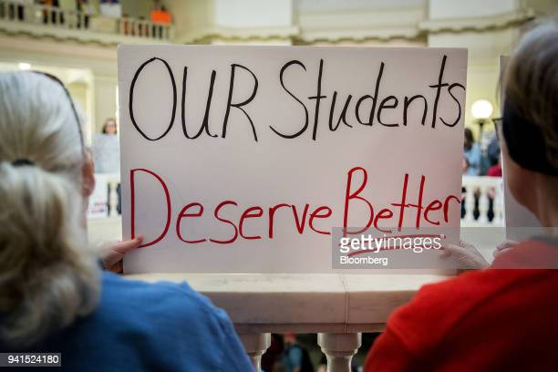 Demonstrators hold a sign reading Our Students Deserve Better during a rally inside the Oklahoma State Capitol building in Oklahoma City Oklahoma US...