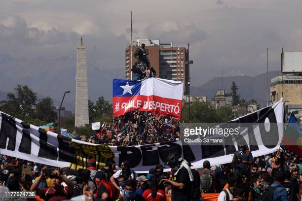Demonstrators hold a sign that reads 'Chile is awake' during the fifth day of protests against President Sebastian Piñera on October 22 2019 in...
