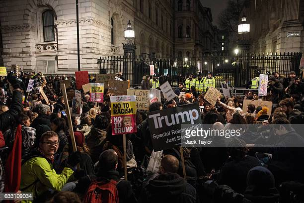 Demonstrators hold a sitting protest outside Downing Street against US President Donald Trump's ban on travel from seven Muslim countries on January...
