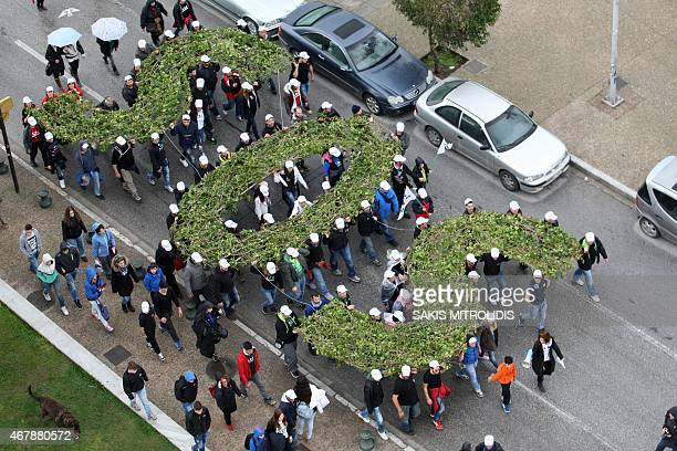 Demonstrators hold an SOS made from tree branches in Thessaloniki on 28 March 2015 as they protest against gold mine extensions in the northern Greek...